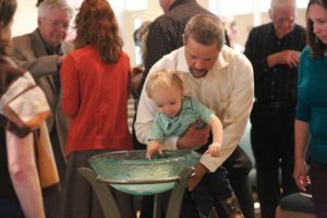 Father lifting son to place their pledge in the baptismal font
